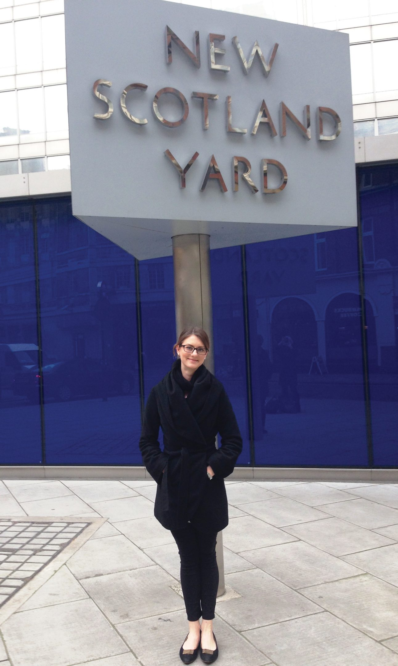 Joana Cook poses at the Scotland Yard sign in front of the Curtis Green Building on the Victoria Embankment.