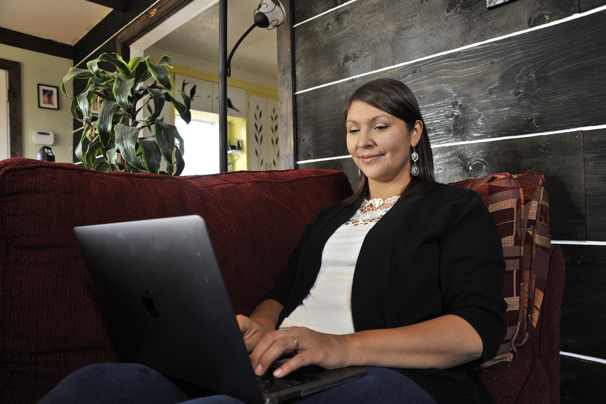 Michelle Brass sits back on a couch writing on a laptop in her home.