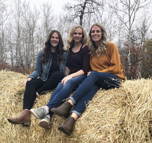 Katelyn, Danielle and Larissa Major sit on a hay bale.