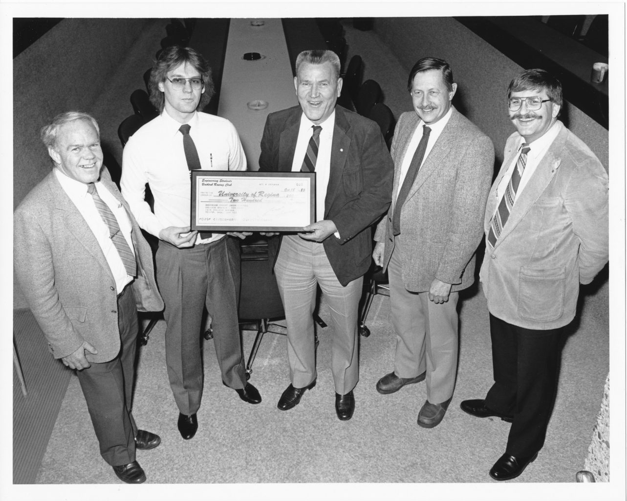 Engineering faculty members and then U of R president Lloyd Barber present the Bathtub Club cheque in 1985.