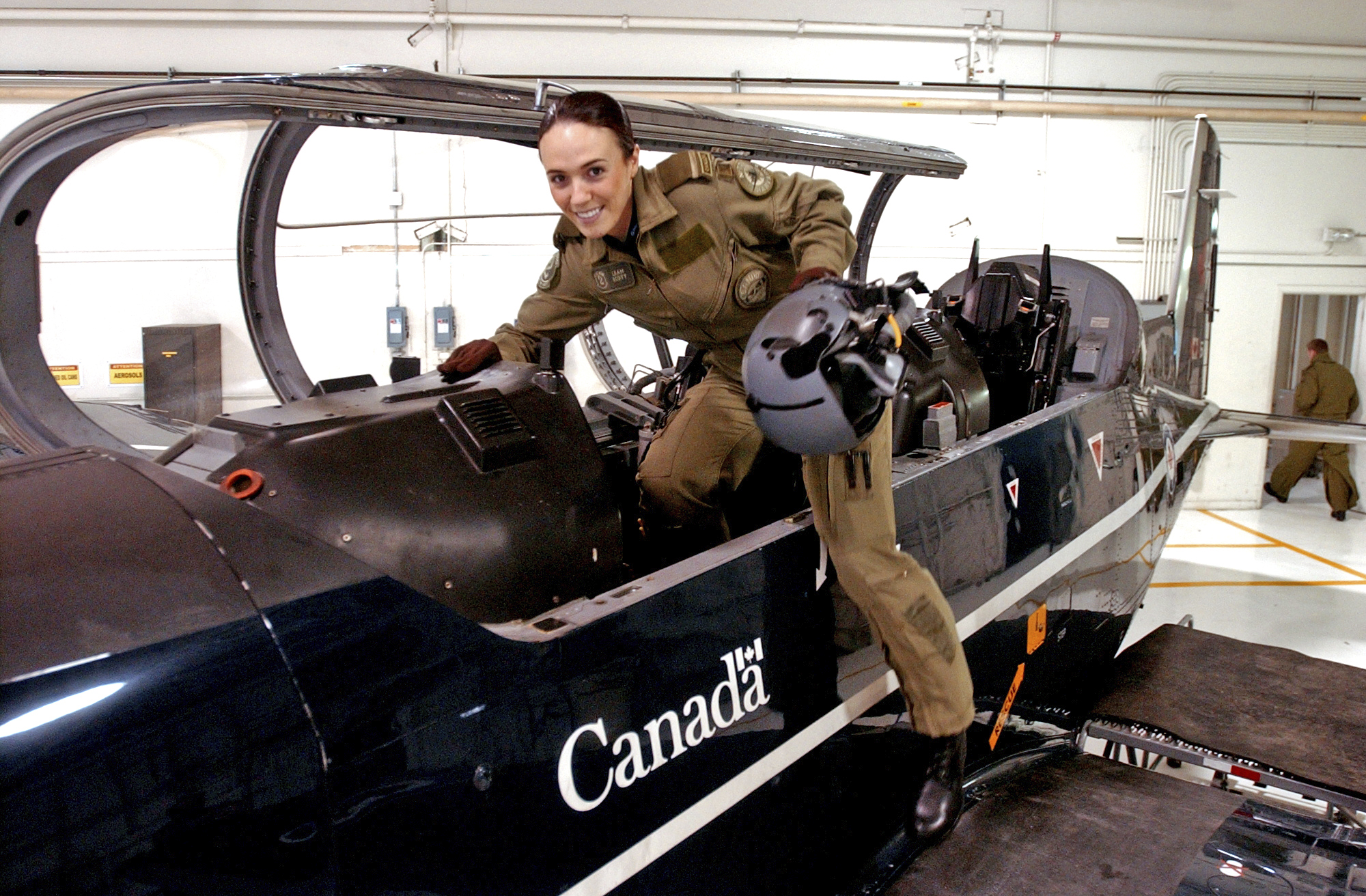 <small>Second Lieutenant Leah Scott climbs into the cockpit of a Harvard aircraft before a flight at 15 Wing Moose Jaw. Shot for 