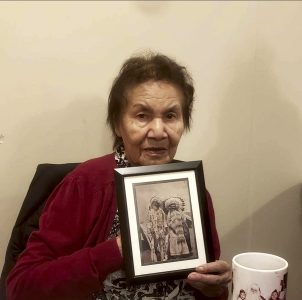 Benjoe's mother Yvonne is a Residential School survivor, as were her parents and grandparents. She holds a photo of her grandparents, Bob Obey and Mary Emily, who helped raise her.
